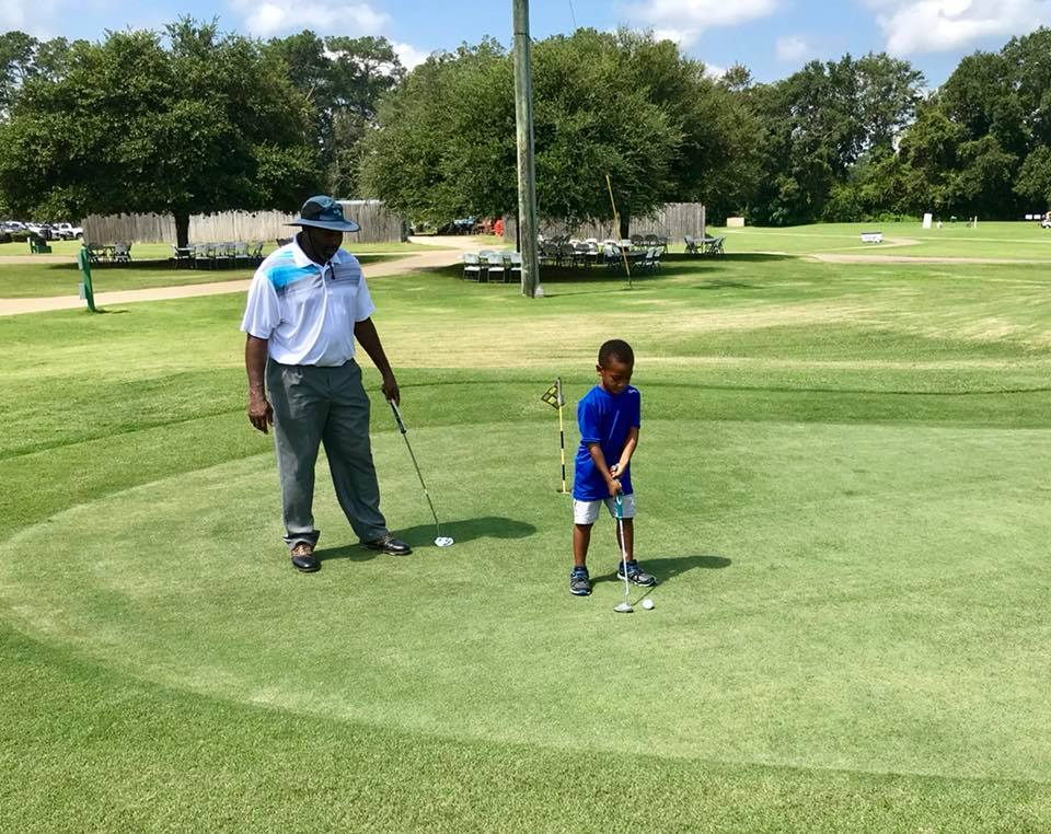 PGA Professional Mike Owens instructs a young student