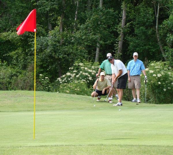 Group of golfers looking at a putt at one of our golf tournaments
